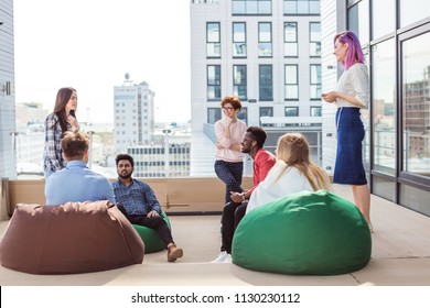 Young creative multiethnic people gesturing and discussing something with coworkers while sitting at the office lounge zone on soft poufs