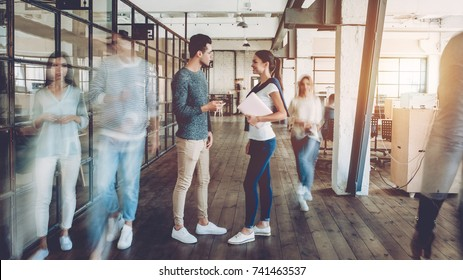 Young creative people in modern office. Successful hipster team in coworking. Businesspeople walking in the corridor of an business center. Motion blur. Couple of freelancers are discussing new ideas.