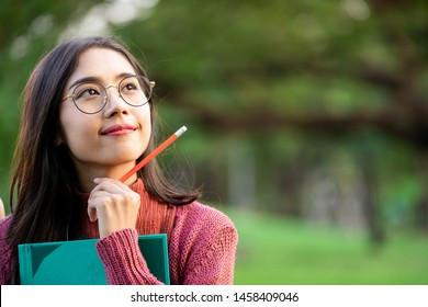 Young creative student girl thinking or planning future education while holding pencil in hand. Creativity idea and learning concept.