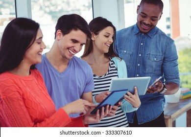 Young creative team looking at phones and tablets in casual office