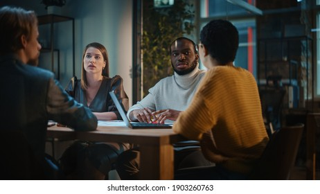 Young Creative Team Meeting with Business Partners in Conference Room Behind Glass Walls in an Agency. Colleagues Sit Behind Conference Table and Discuss Business, App User Interface and Design.