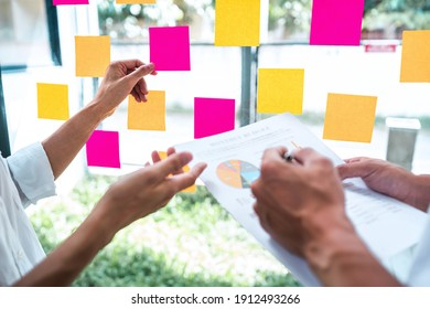 Young creative team professional using post it notes in glass wall to writing strategy business plan to development grow to success.