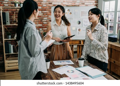 Young creative team work colleagues ladies discussing ideas in board room. Group of asian female people during start up business meeting in studio. three coworkers girls laughing and talking.