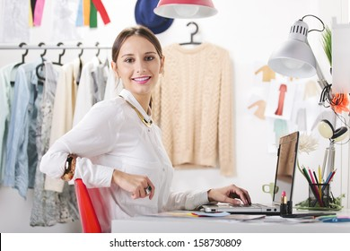 Young creative woman in her office looking at camera./ Fashion woman blogger working in a creative workspace.