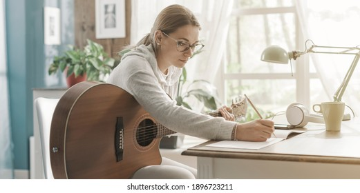 Junge kreative Frau, die zu Hause Gitarre spielt und Musik komponiert