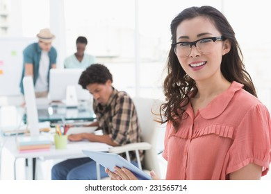 Young creative woman using her tablet in creative office