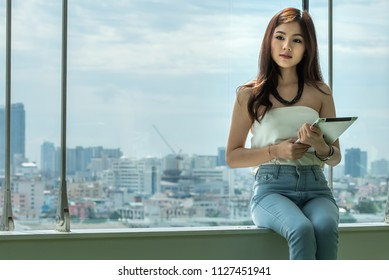 Young creative and working businesswoman holding tablet in relaxing time and working on tablet computer at the new modern style office glasses building, new technology equipment concept.