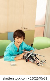 Young creator. Happy schoolboy sitting at the desk showing his helicopter model made of construction set.