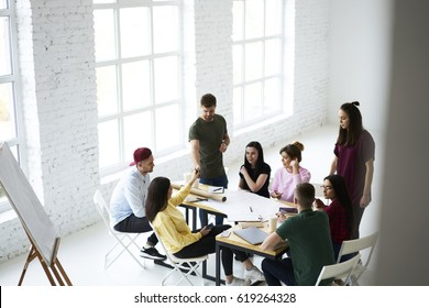 Young crew of skilled designers brainstorming discussing ideas sharing opinions sitting together at desktop, talented colleagues collaborating during informal meeting in modern loft interior office
