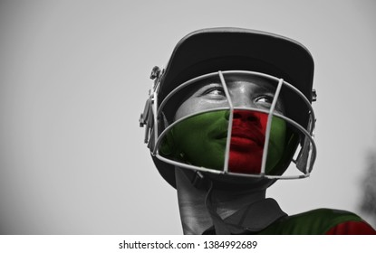 Young cricketer painted green and red colours on face standing in a place