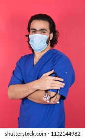young cross arms doctor wearing muzzle and holding stethoscope while looking to camera , in a pink background