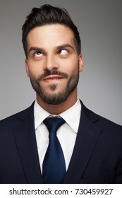 young cross eyed businessman  biting his lip and looks up on grey background
