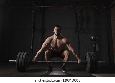 Young cross fit athlete lifting barbell at gym. Muscular shirtless man doing functional training. Deadlift exercise.
