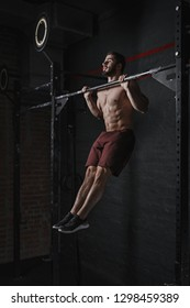 Young crossfit athlete doing pull-ups at the gym. Strong man doing functional training. Workout exercises. Calisthenics practicing