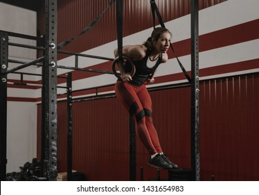 Young crossfit woman doing muscle-ups on gymnastic rings at the gym. Strong female athlete doing ring dips while functional training. Practicing calisthenics.
