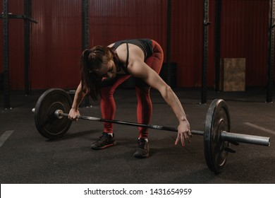 Young crossfit woman preparing barbell for lifting weight at the gym. Female athlete doing functional training.