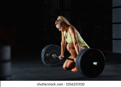Young crossfit woman preparing for her weightlifting workout with a heavy dumbbell. Beautiful fitness woman concentrating before performing deadlift at crossfit box. Crossfit and fitness