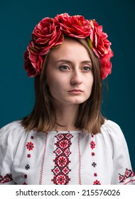 Young crying girl in the Ukrainian national suit on a blue background