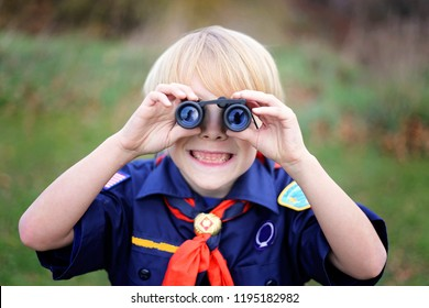 A young Cub Scout in the tiger den is smiling as he looks at the camera through small binoculars outside on a summer day.