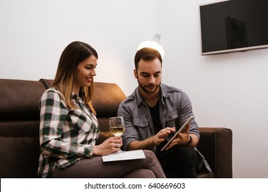 Young cuple using tablet and drinking wine in the living room.