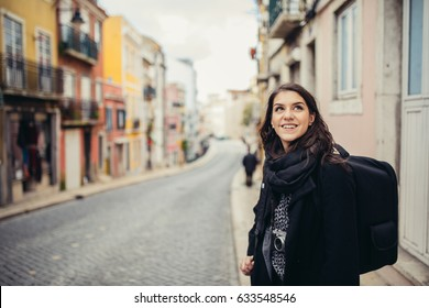 Young curious woman travelling and visiting Europe.Backpacker touring Europe and Mediterranean culture.Colourful streets of Lisbon,Portugal.Budget traveling and exploring concept.Cheap trips concept