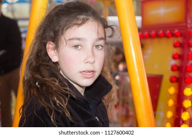 a young curly girl at the fun fair