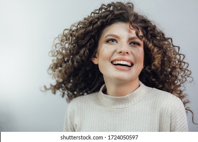 Young curly girl smiling in a white sweater