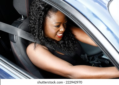 Young Curly Hair Black Woman in Sleeveless Driving a Car in Safety Seat Belt.