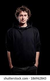 Young curly hair caucasian man wearing black hooded sweatshirt. Low key portrait taken on black background.