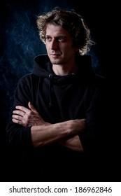 Young curly hair caucasian man wearing black hooded sweatshirt. Low key portrait taken on black background full of smoke.