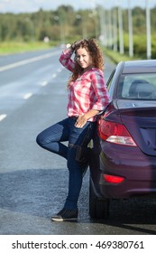 Young curly hair Caucasian woman standing near own car on the asphalt road