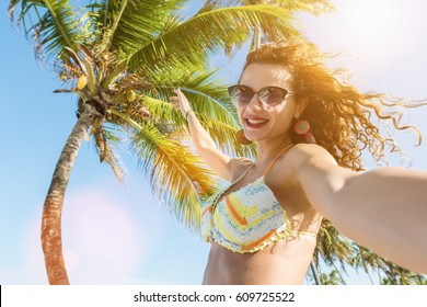 Young curly hair girl taking self portrait selfie on the tropical beach.Lens flare