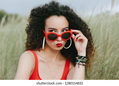 Young curly hair pensive girl puckering her lips and wearing retro red sunglasses. Pop summer fashion.