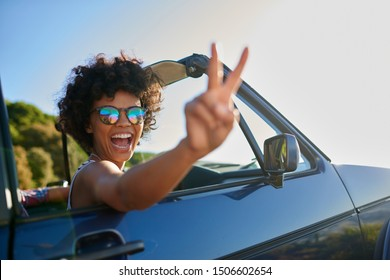 Young curly hair woman enjoying road trip in a convertible car
