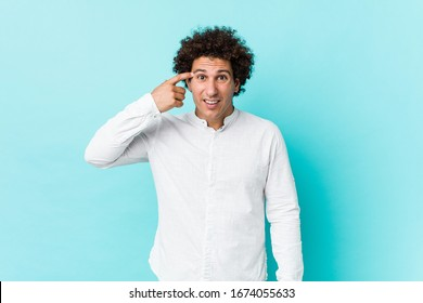 Young curly mature man wearing an elegant shirt showing a disappointment gesture with forefinger.