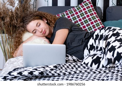 ein junger, lockerer Teelich mit Teddybär schlief im Bett neben einem Laptop ein