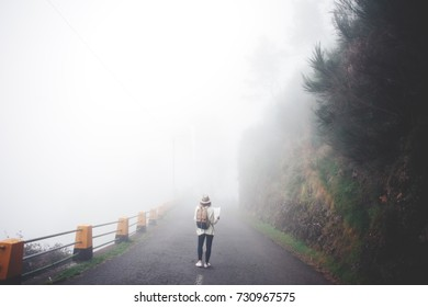 Young curly traveling girl wearing backpack and hat standing on the road in fog, searching path and using map.