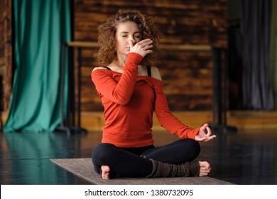 Young curly woman doing yoga exercises, using nadi shodhana pranayama