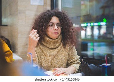 young curly woman eating in fast food with friends– hungry, conviviality, sharing