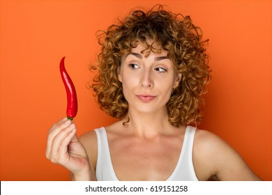 young curly woman on orange background with chili pepper
