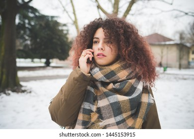 young curly woman talking with smartphone outdoor – winter day, communication, seriousness