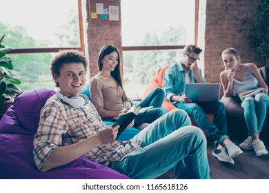 Young curly-haired guy sits on purple chair with book in his hands and looks at the camera on the background of people in jeans denim casual stylish wear who are busy with lessons