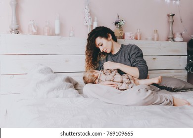 A young curly-haired mother in a gray sweater is breast-feeding her daughter on a trendy pink background in the Christmas and New Year's interior. Holiday. Family concept.