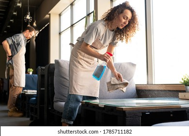 Young curly-haired waitress in apron spraying detergent while bussing tables in cafe before opening