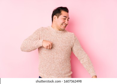 Young curvy man posing in a pink background isolated dancing and having fun.