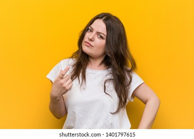 Young curvy plus size woman pointing with finger at you as if inviting come closer.
