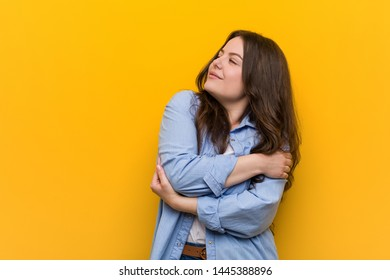 Young curvy plus size woman hugs himself, smiling carefree and happy.