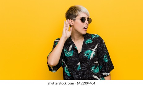Young curvy woman wearing a summer look trying to listening a gossip.
