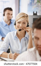 Young customer service operators working in office, smiling.