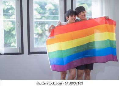 Young cute asian gay couple smiling standing and hold rainbow flag.teens homosexual couple.LGBTQ Concept.Love and Relationships